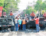 Thai citizens inspect the remnants of the Thai military equipment deployed against red-shirt protesters - Songkran in Bangkok