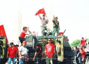 Red-shirt protesters clamor over abandoned Thai military hardware in front of Democracy Monument.