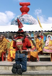 A red-shirt protester kneels before Buddhist monks, Bangkok's Democracy Monument draped in red in the background