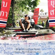 A young boy sits on an abandoned Thai Armored Personnel Carrier immobilized by red-shirt protesters, Songkran 2010. Photo: John Le Fevre